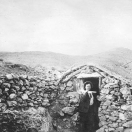 Miner standing next to his home made of rocks - Randsburg
